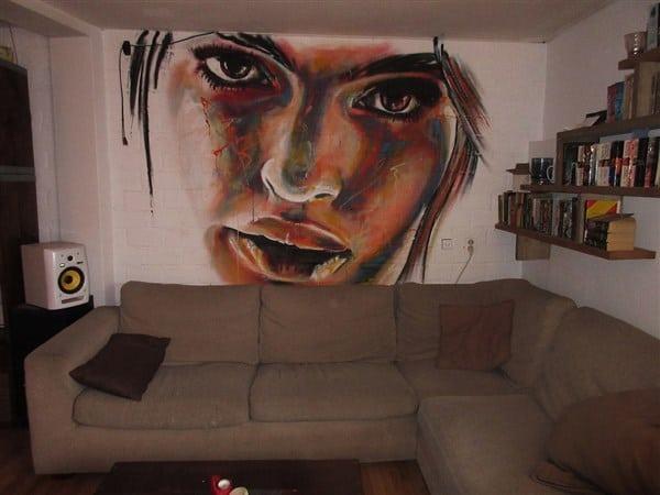 muurschildering in woonkamer achter bank portret ratajkovski model ogen kleur experimenteel realistisch Timbert kunstwerk
