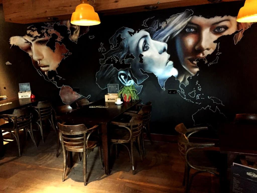 muurschildering cafe broer van portretten in wereldkaart op zwarte achtergrond geschilderde vrouwen door Timbert