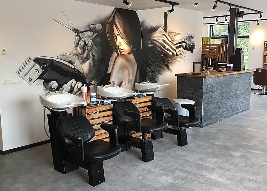Muurschilderinger kapperszaak Snoeischerp in Beilen Drenthe spuitbus en stift vrouw en knippende handen fullwidth