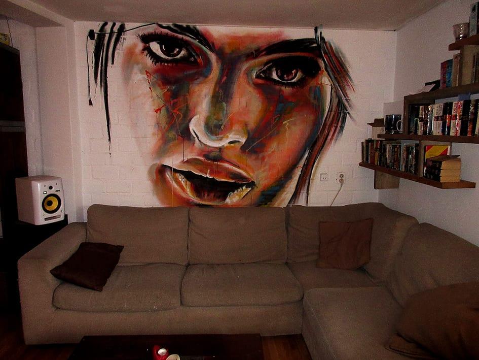 muurschildering portret model in kleur boven de bank. gemaakt met spuitbus en stift op acryl en waterbasis door timbert